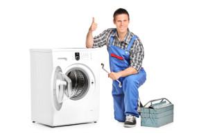 Thợ sửa cho ngón tay cái lên bên cạnh một máy giặt